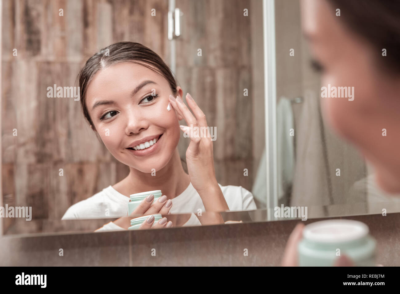 Pleasant appealing woman using face cream in the morning - Stock Image