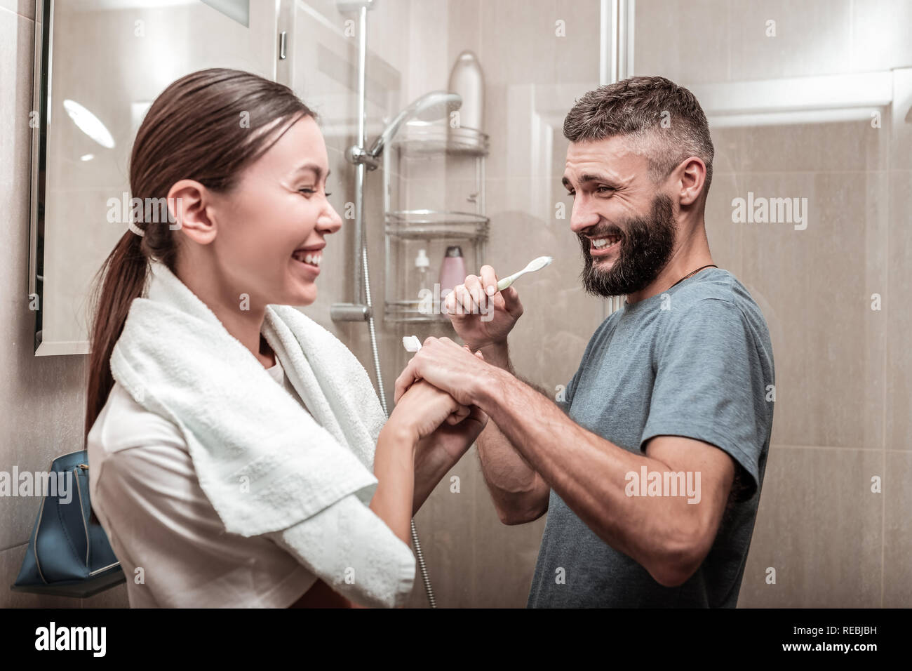 Dark-haired woman using cream for sensitive skin looking into mirror - Stock Image
