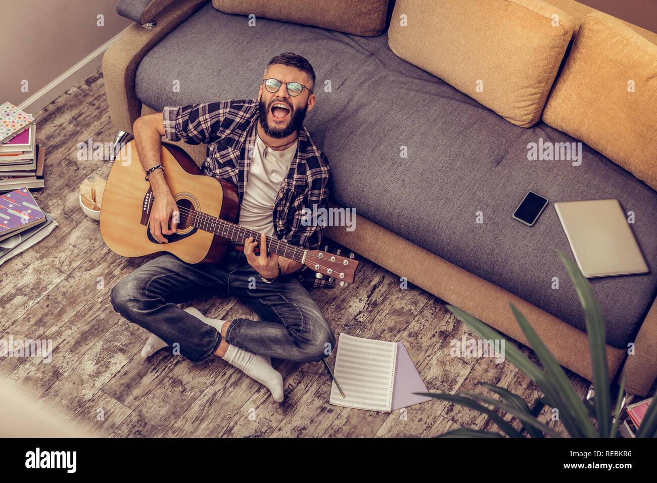 Creative positive nice man rehearsing a song - Stock Image