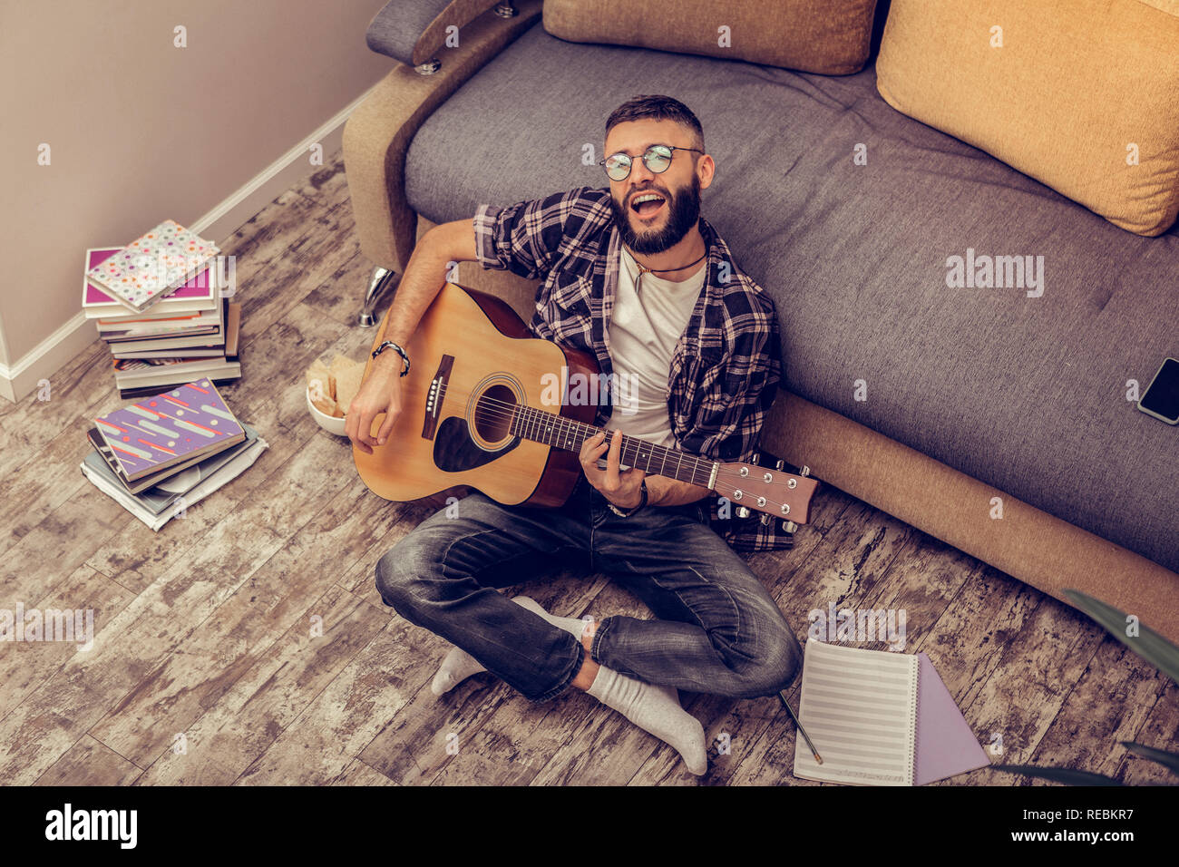 Creative talented musician playing the guitar at home - Stock Image