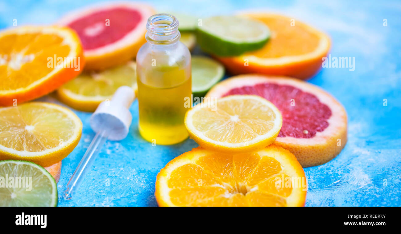 Citrus oil bottle with lime, orange, lemon and grepfruit slices