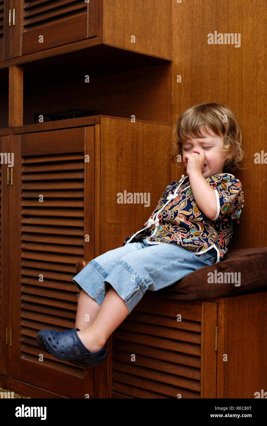 Two year old girl having a tantrum sitting on 'naughty chair - Stock Image