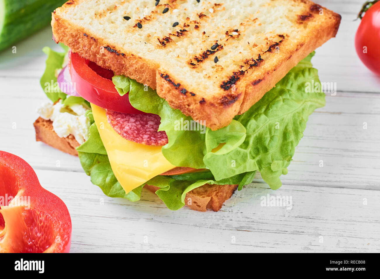 sandwiche with ham, lettuce and fresh vegetables on white background close up - Stock Image