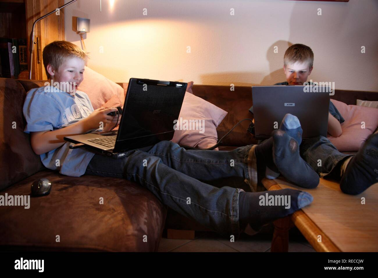 Brothers, 11 and 13 years old, with laptop computer in the living room, playing a car racing computer game on two computers Stock Photo