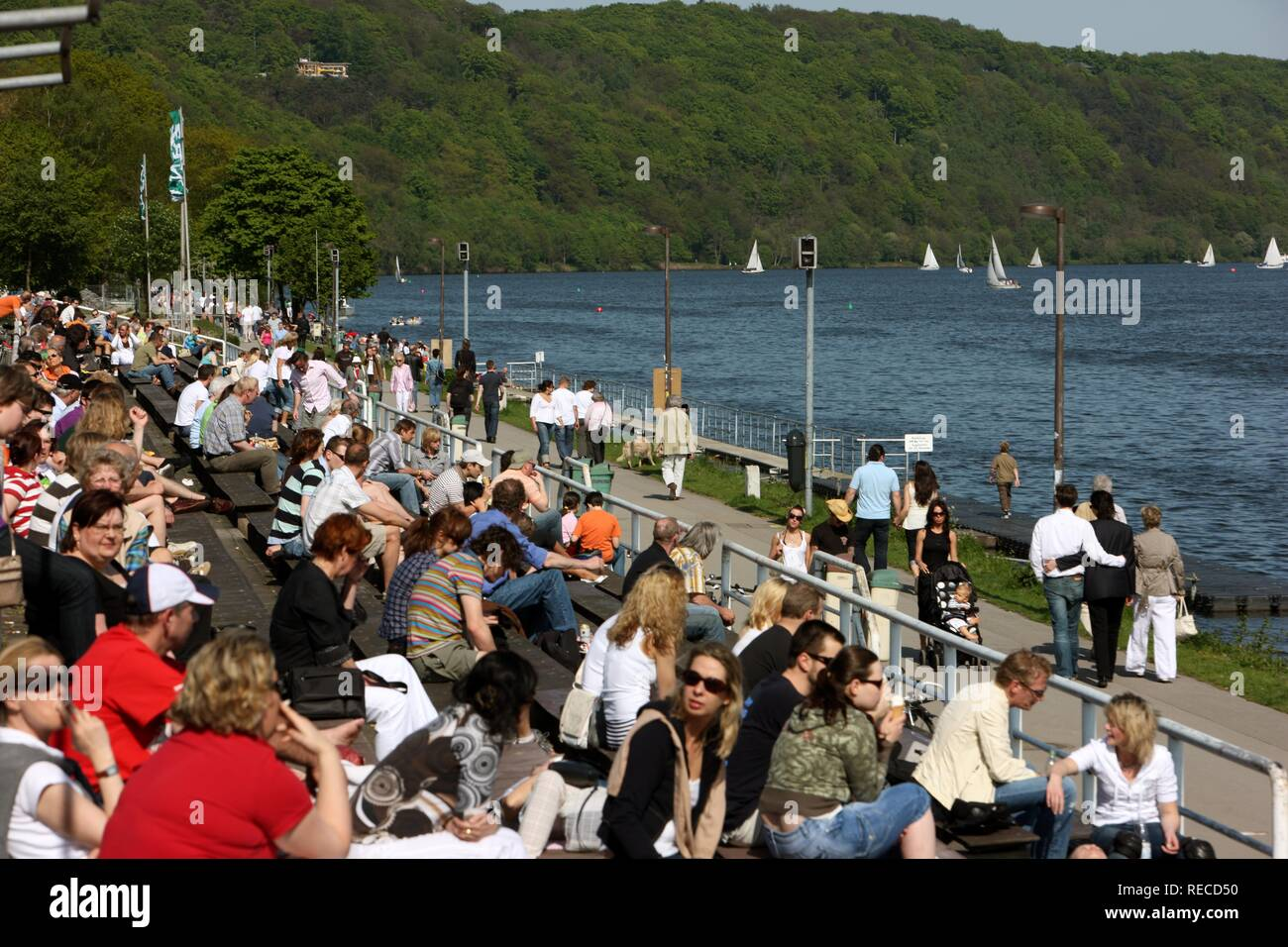 People in the summer on the stands of the regatta course on the Baldeneysee storage lake, river Ruhr, Essen - Stock Image