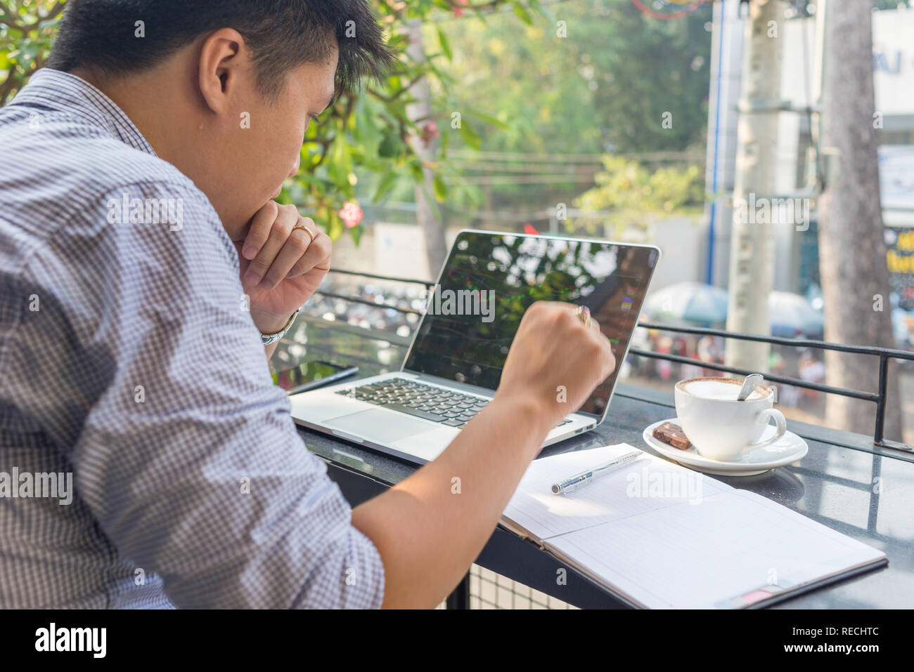 Asian investor watching the change of stock market on laptop Stock Photo