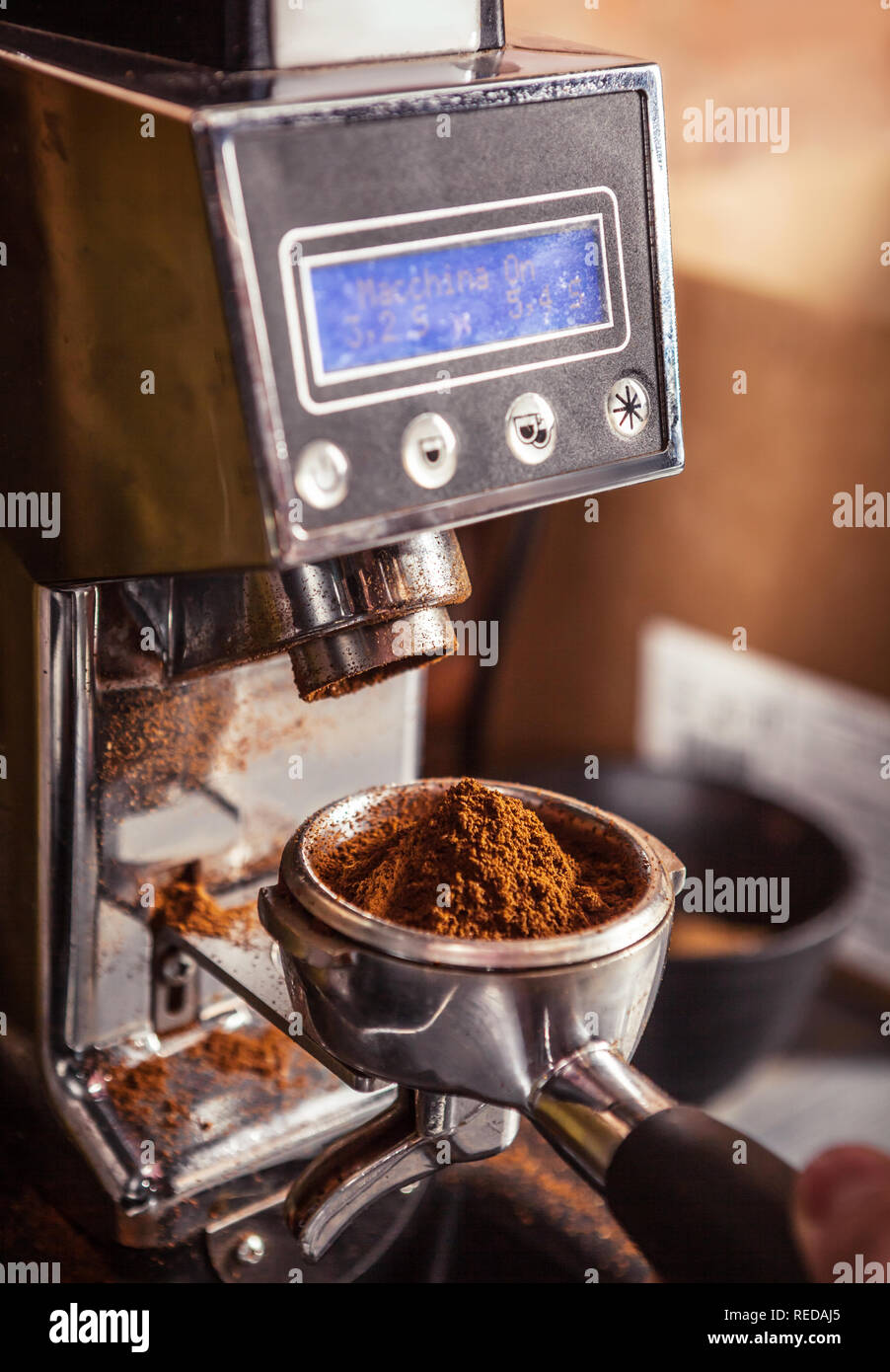 Cropped image of barista using coffee grinder holding portafilter with ground coffee. Stock Photo