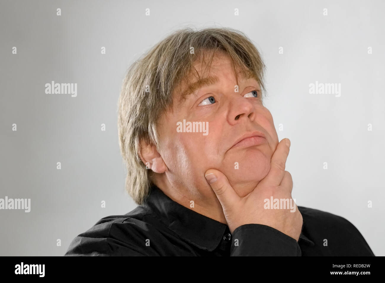 50 year old man with fair skin and blond hair is at a loss. The face shows a lot of facial expressions when thinking. He put his hand under his chin a - Stock Image