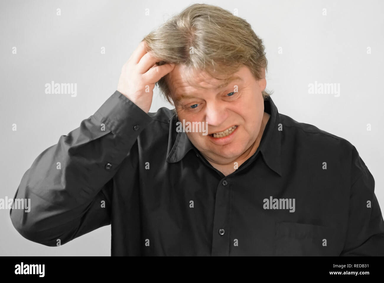 50 year old man with fair skin and blond hair is at a loss. The face shows a lot of facial expressions when thinking. He scratches his head to remembe - Stock Image