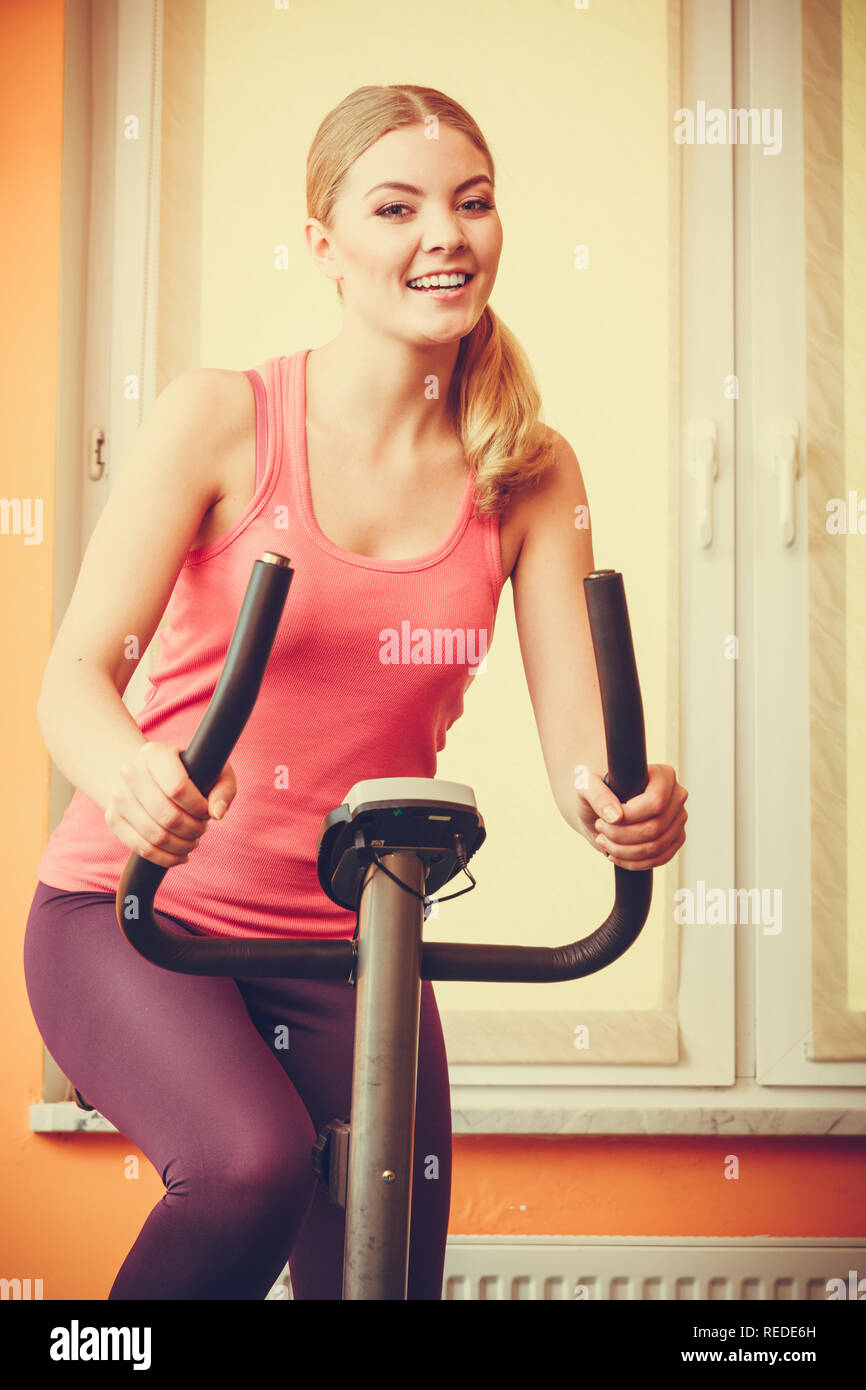 Active young woman working out on exercise bike stationary