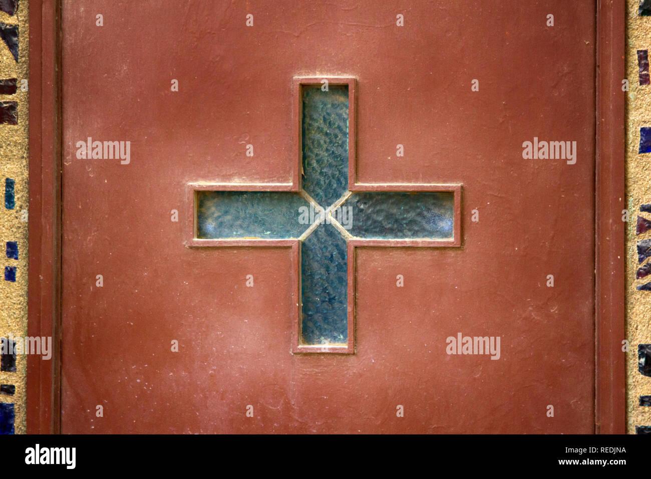 Catholic glazed Cross on the Church door. True Cross Stock Photo