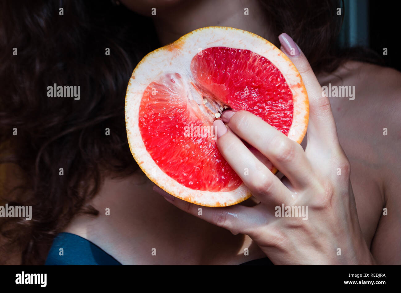 A woman is holding a grapefruit by her body. Concept masturbation Stock Photo