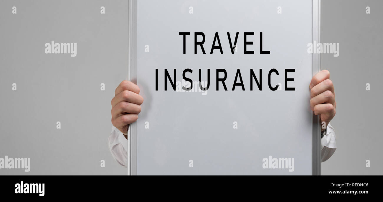 men's hands holding a poster with the inscription travel insurance isolated on light background - Stock Image