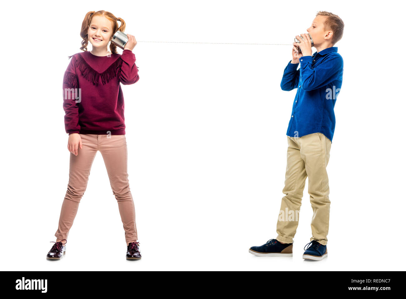 smiling kids play with tins connected by rope isolated on white - Stock Image