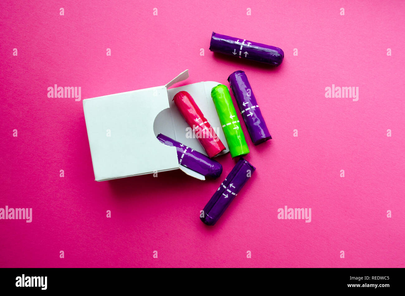 white box with multi-colored tampons on a pink background Stock Photo