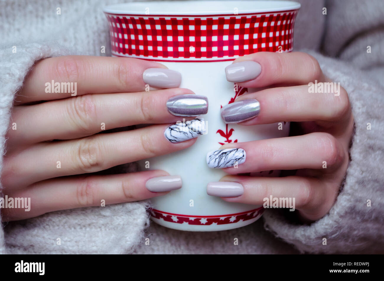 the woman in the sweater is holding a mug. A beautiful professional manicure with a metal and marble coating. Stock Photo