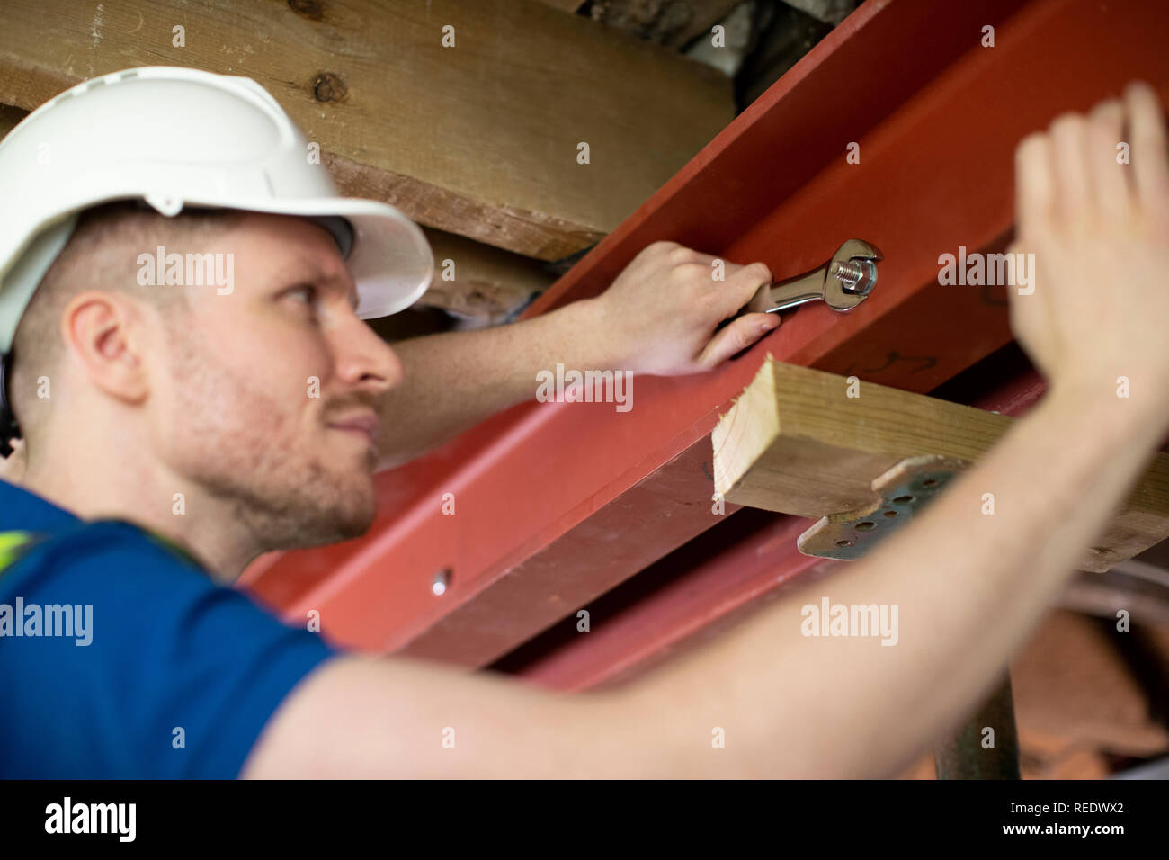 Construction Worker Fitting Steel Support Beam Into Renovated House Ceiling - Stock Image
