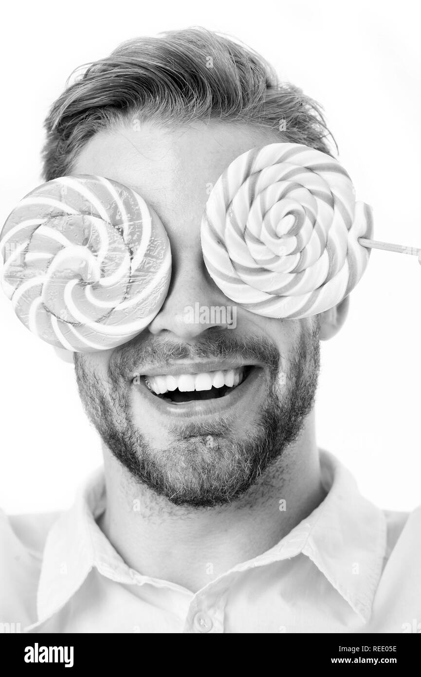 Guy hypnotized by sweets close up. Impressing fact sugar nutrition. Man handsome bearded guy holds lollipop candy. Man with lollipop looks hypnotized. Healthy nutrition and sugar addiction concept. - Stock Image