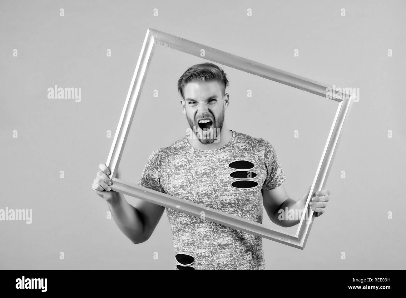 Man shout with picture frame on grey background. Angry macho with beard hold wooden photo frame. Guy with empty framework. Creativity and wall art concept. - Stock Image