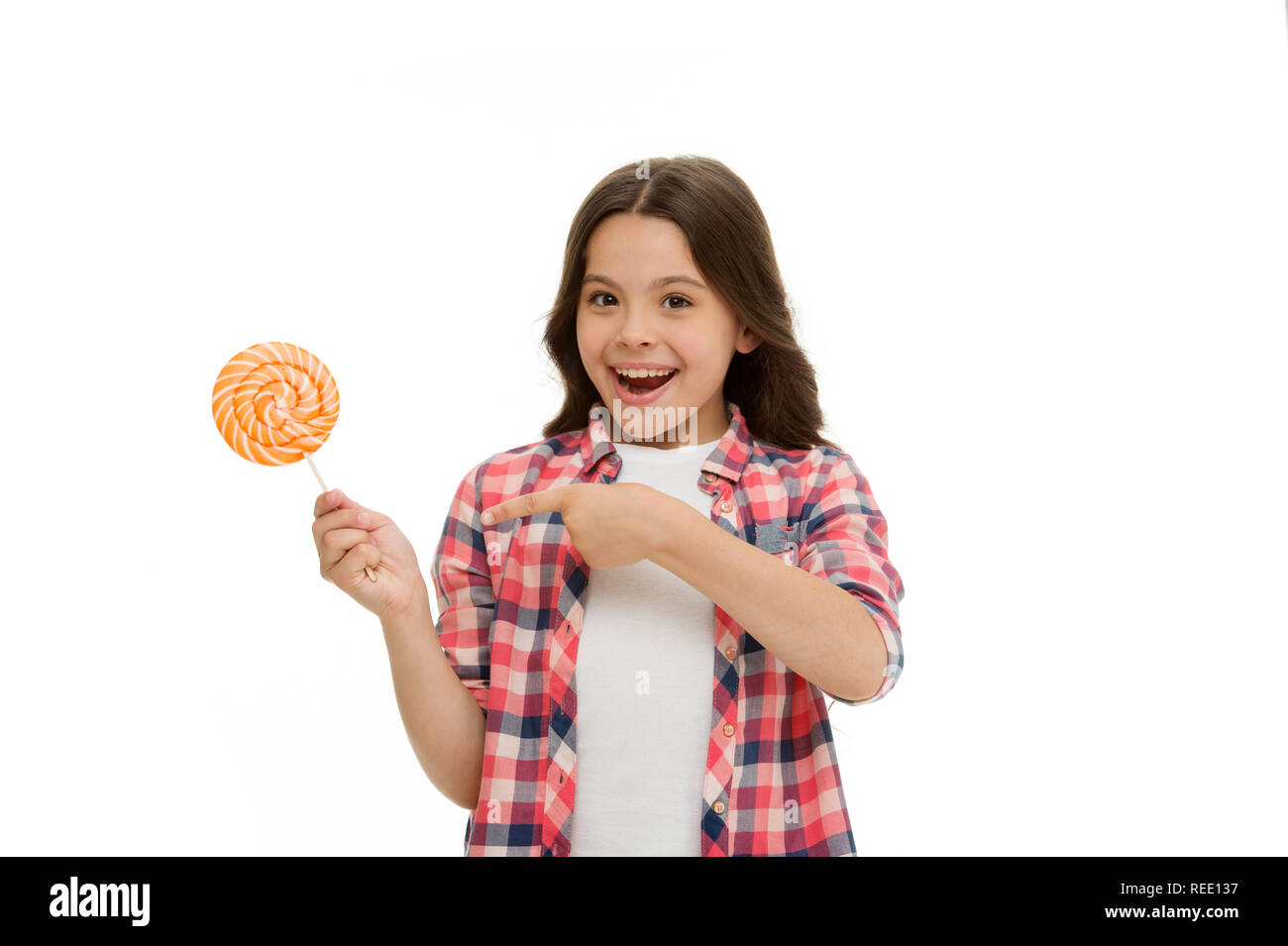 Impressing fact sugar nutrition. Girl child smiling holds lollipop candy. Girl kid with lollipop looks surprised. Healthy nutrition and dieting concept. Surprising effect sugar. Holiday sweet treats. - Stock Image