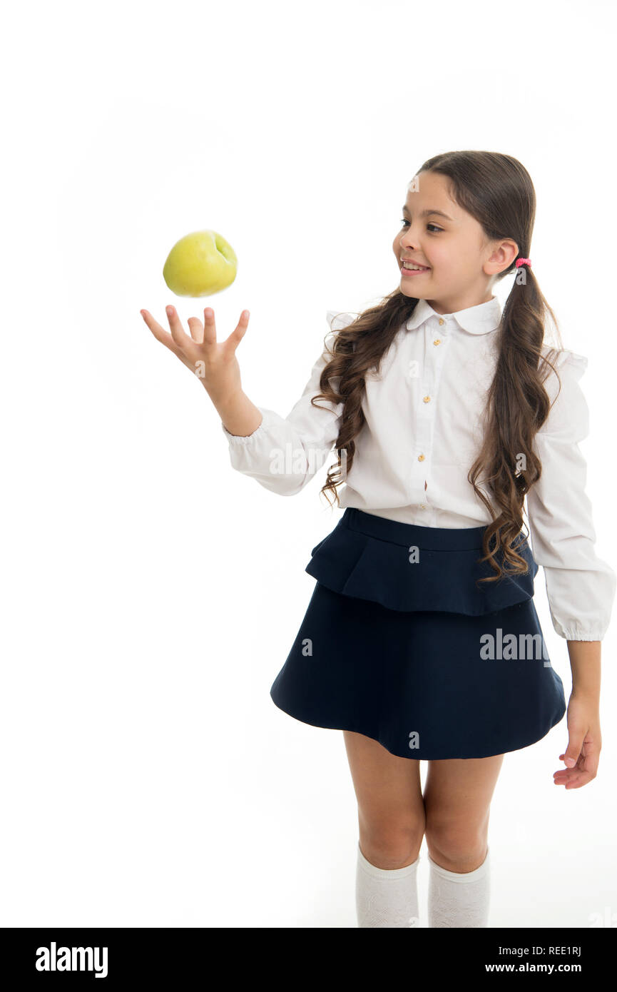 Child girl school uniform clothes toss apple. Girl cute pupil holds apple fruit white background. Child smart kid smiling face choose healthy snack. School lunch snack concept. Healthy nutrition. - Stock Image