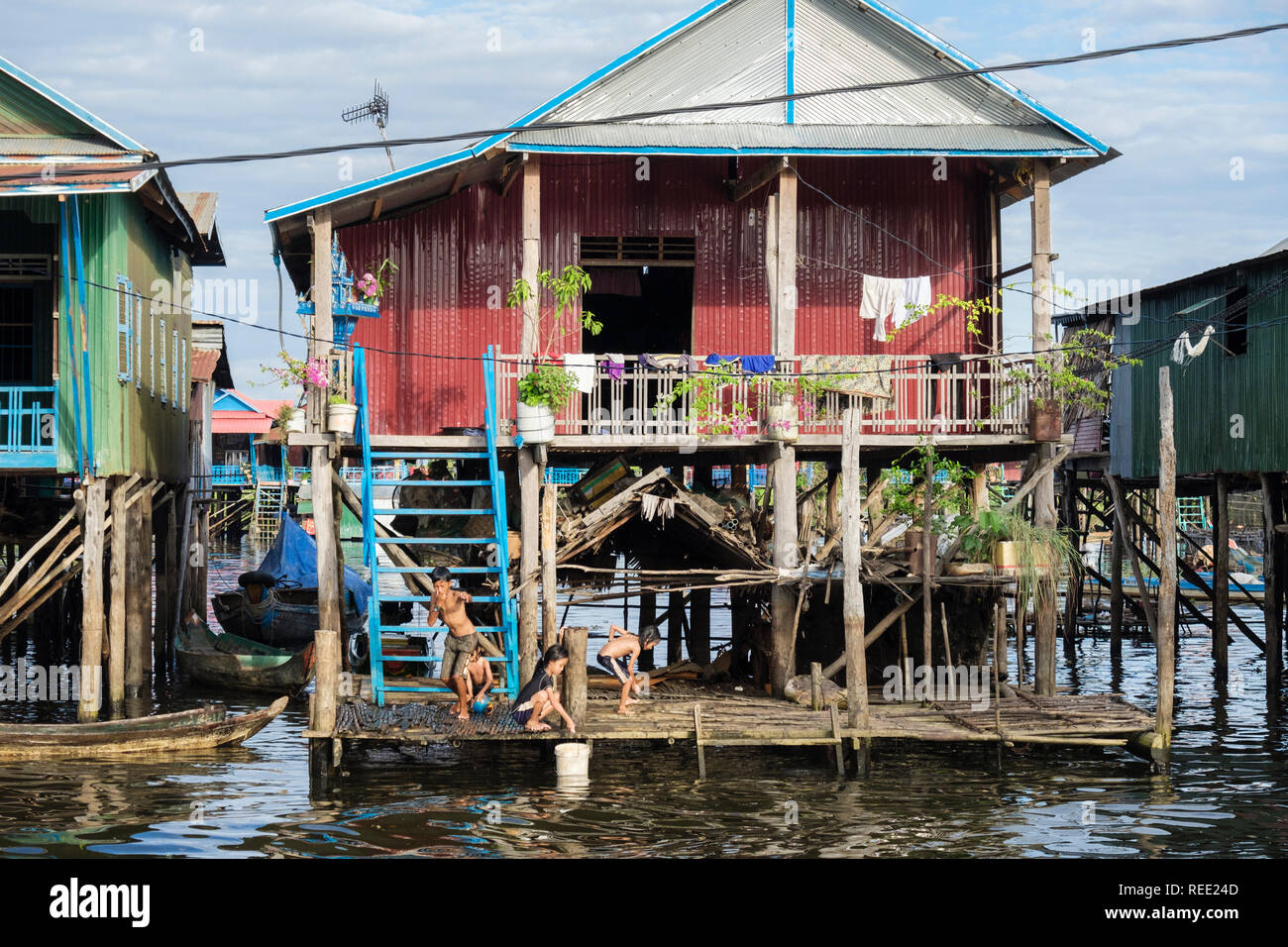 Children playing outside a house on stilts in floating village in Tonle Sap lake. Kampong Phluk, Siem Reap province, Cambodia, southeast Asia Stock Photo