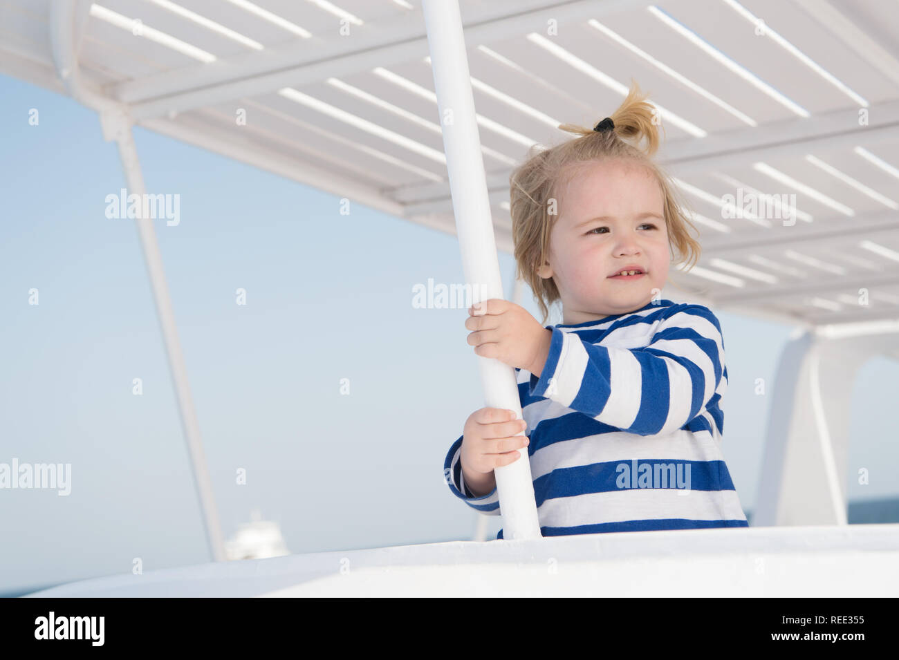 Cruising with kids. Child smiling face striped shirt looks like sailor. Kid boy toddler travelling sea cruise. Family vacation on cruise ship all inclusive tour. Child enjoy vacation on cruise ship. - Stock Image