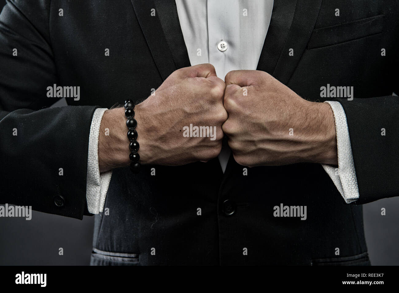 Male fists with swollen veins and bracelet on formal suit background. Confrontation concept. Hand of business person confronts against each other. Symbol of strength of will. - Stock Image