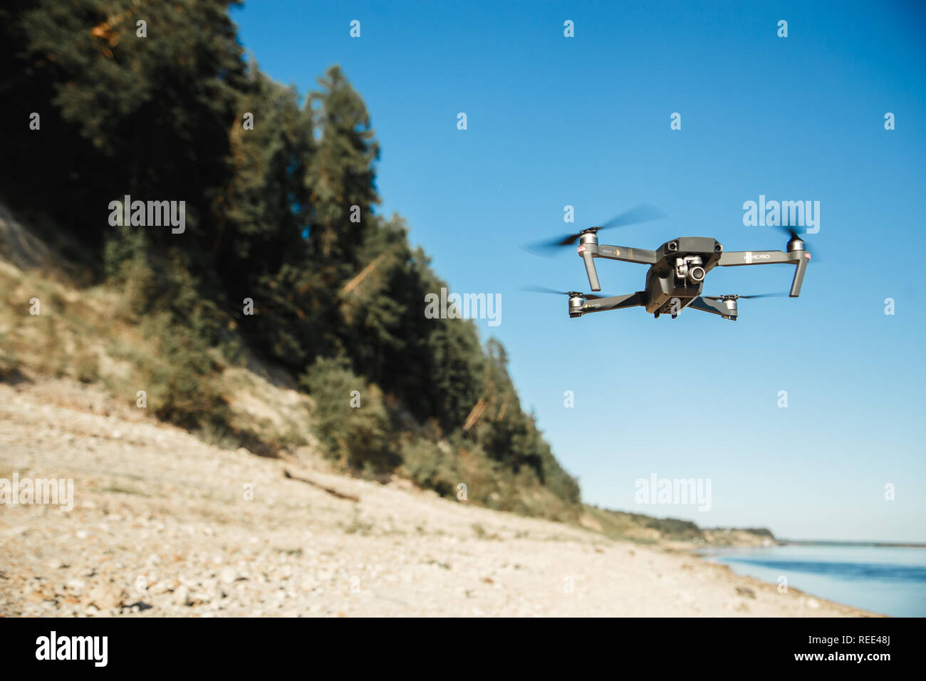 Compact Drone flying over the forest landscape. Flying remote camera. - Stock Image