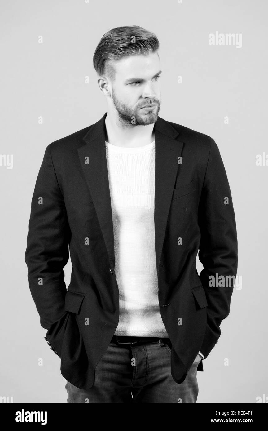 Macho in black jacket pose with hands in jeans pockets. Man with beard on unshaven face on grey background. Fashion, casual style concept - Stock Image