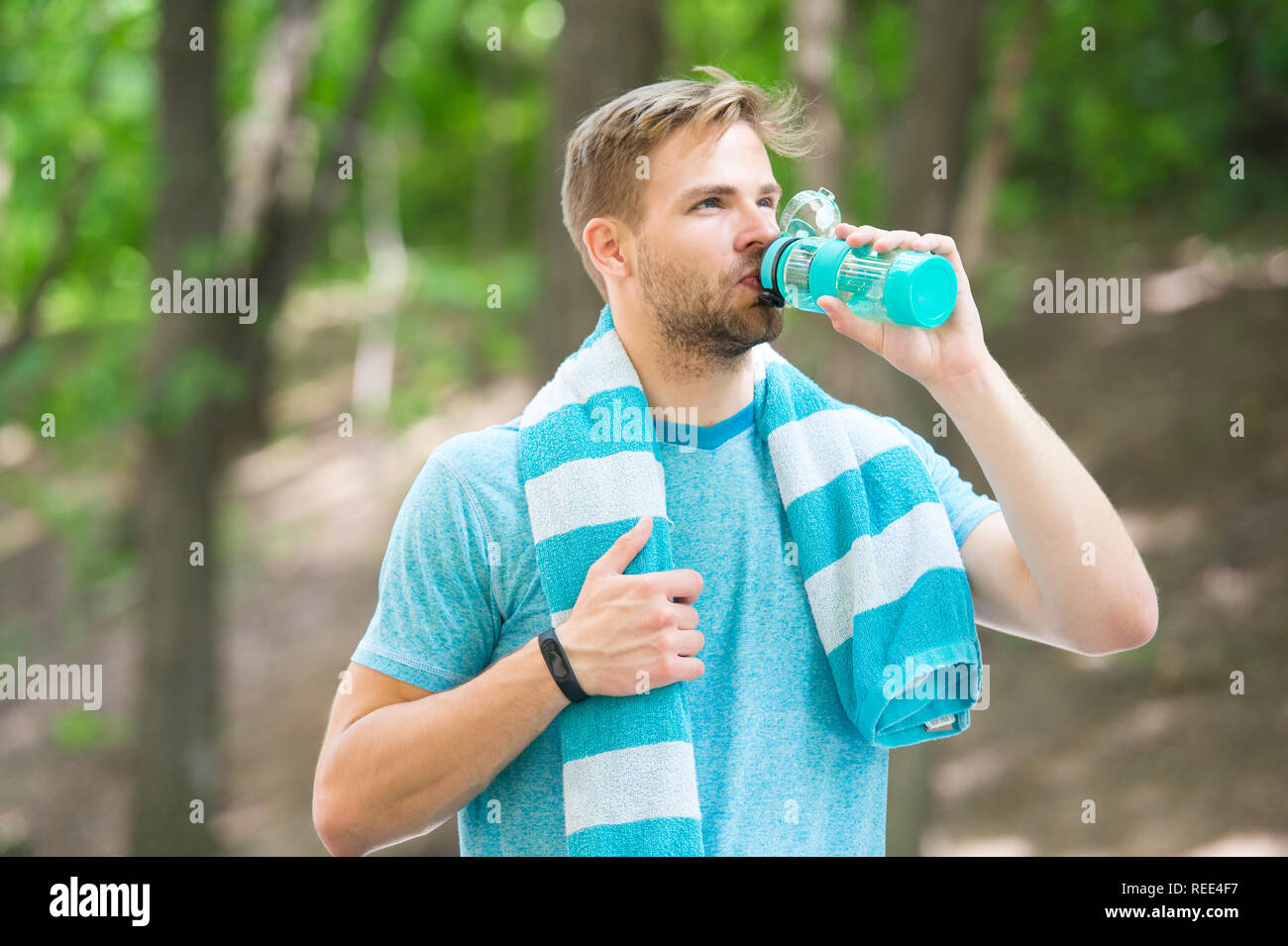 Man with athletic appearance holds bottle with water. Sport and healthy lifestyle concept. Athlete drink water after training at stadium on sunny day. Man athlete in sporty clothes training outdoor. - Stock Image