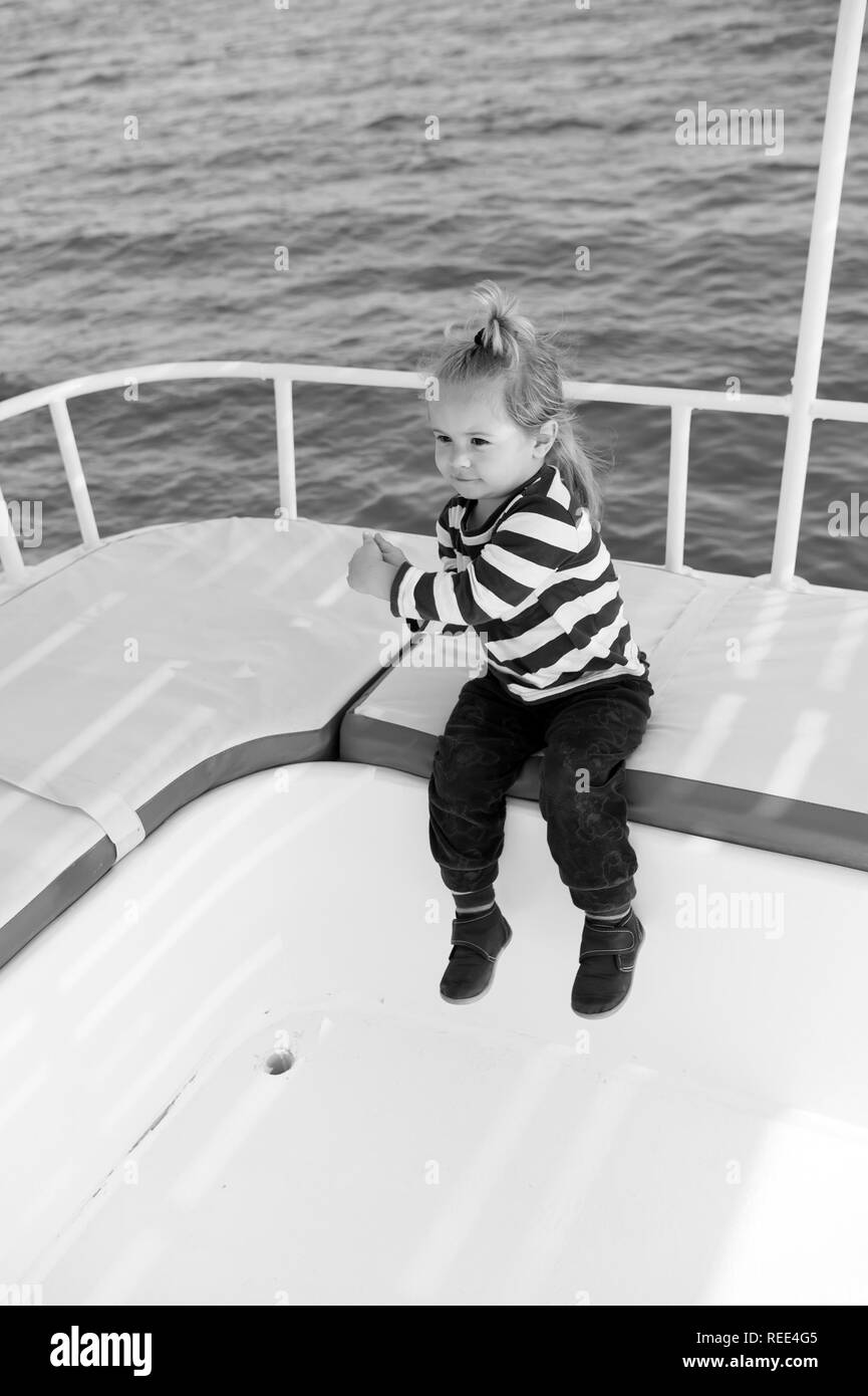 Summer vacation concept. Boy in sailor shirt sail in blue sea. Adventure, discovery, wanderlust. Child with blond hair on yacht on sunny day. Travel destination, cruise, travelling. - Stock Image