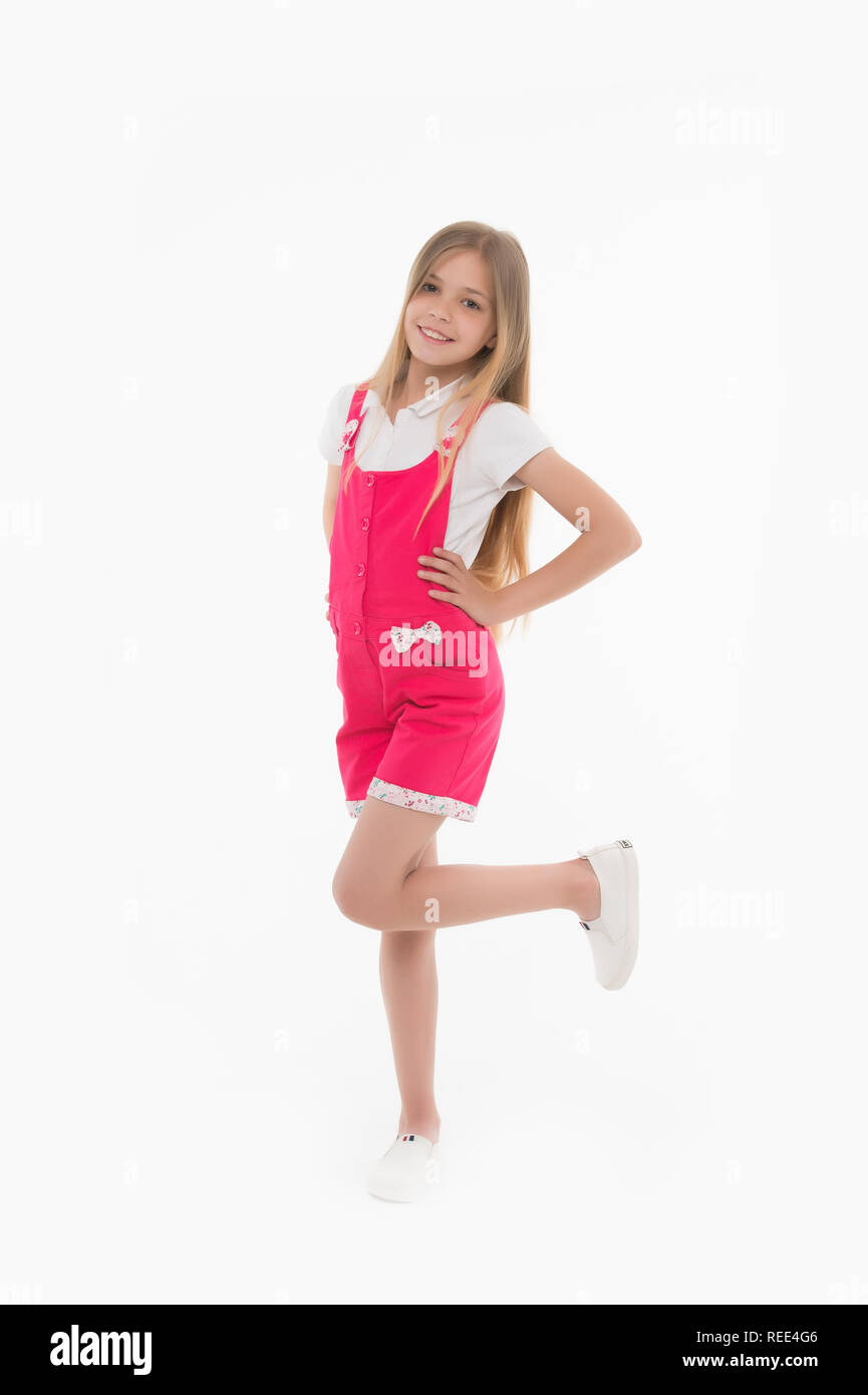 Kid model in fashionable overall. Small girl smile in pink jumpsuit isolated on white. Child smiling with long blond hair. Fashion style and trend. Happy childhood and childcare. - Stock Image