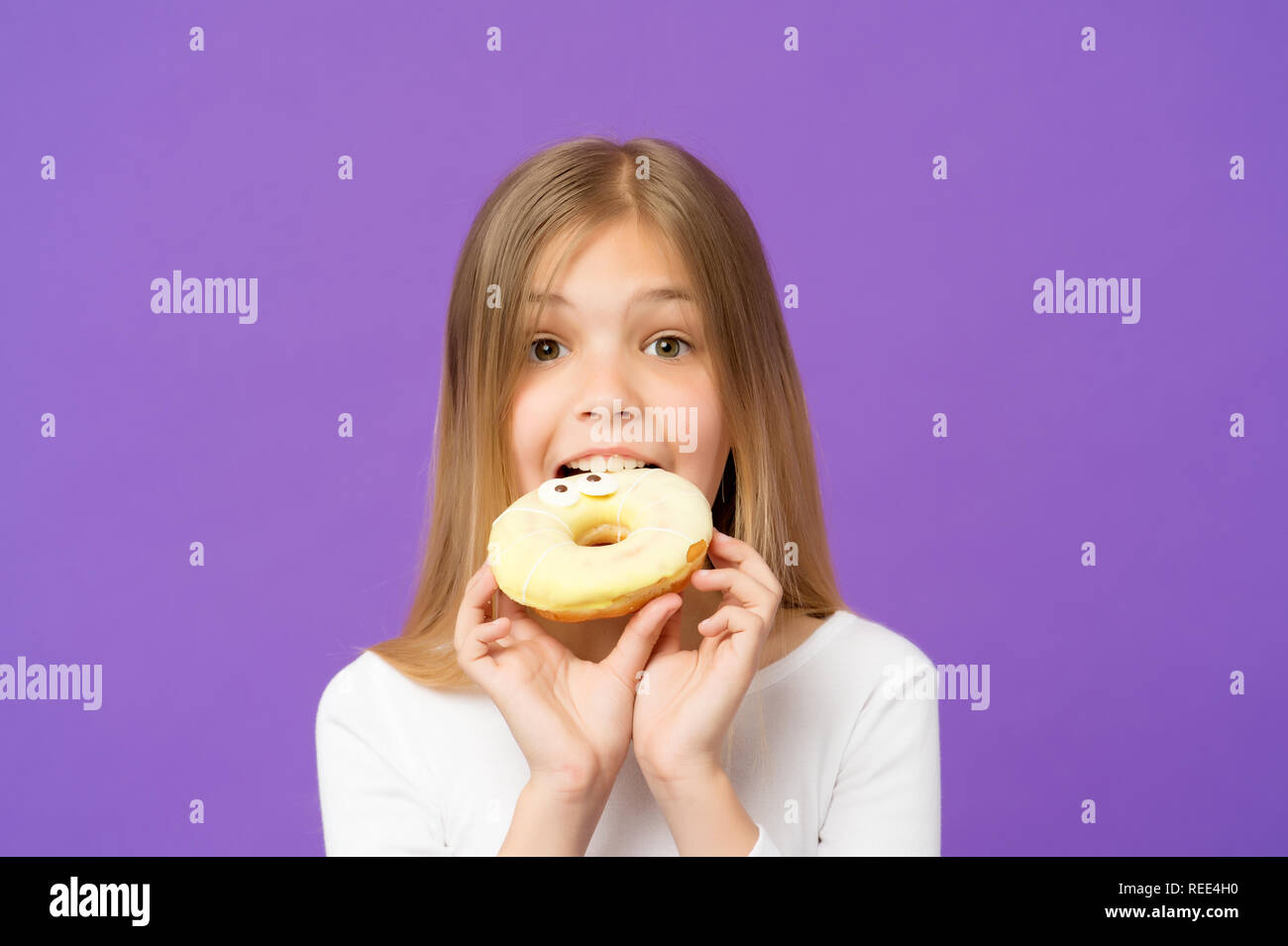 Sweetie beauty. Little girl eat donut on violet background. Child with glazed ring doughnut on purple background. Kid with junk food. Food and dessert. Childhood and childcare, copy space. - Stock Image