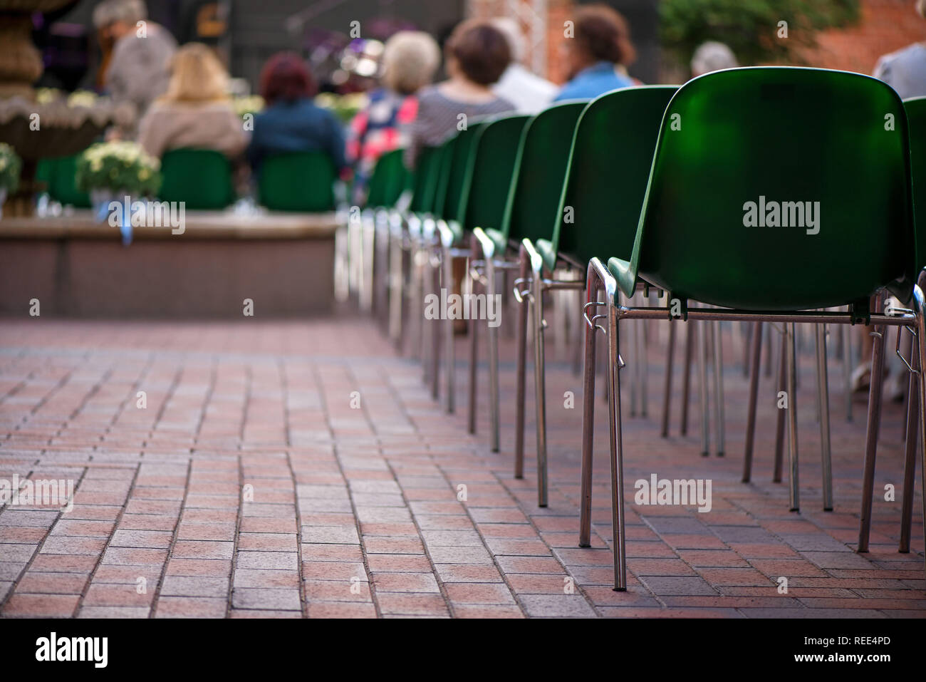 Green chairs in rows next to stage on romantic evening. Setting up the concerts venue and checking the sound before performance. Audience starting to - Stock Image