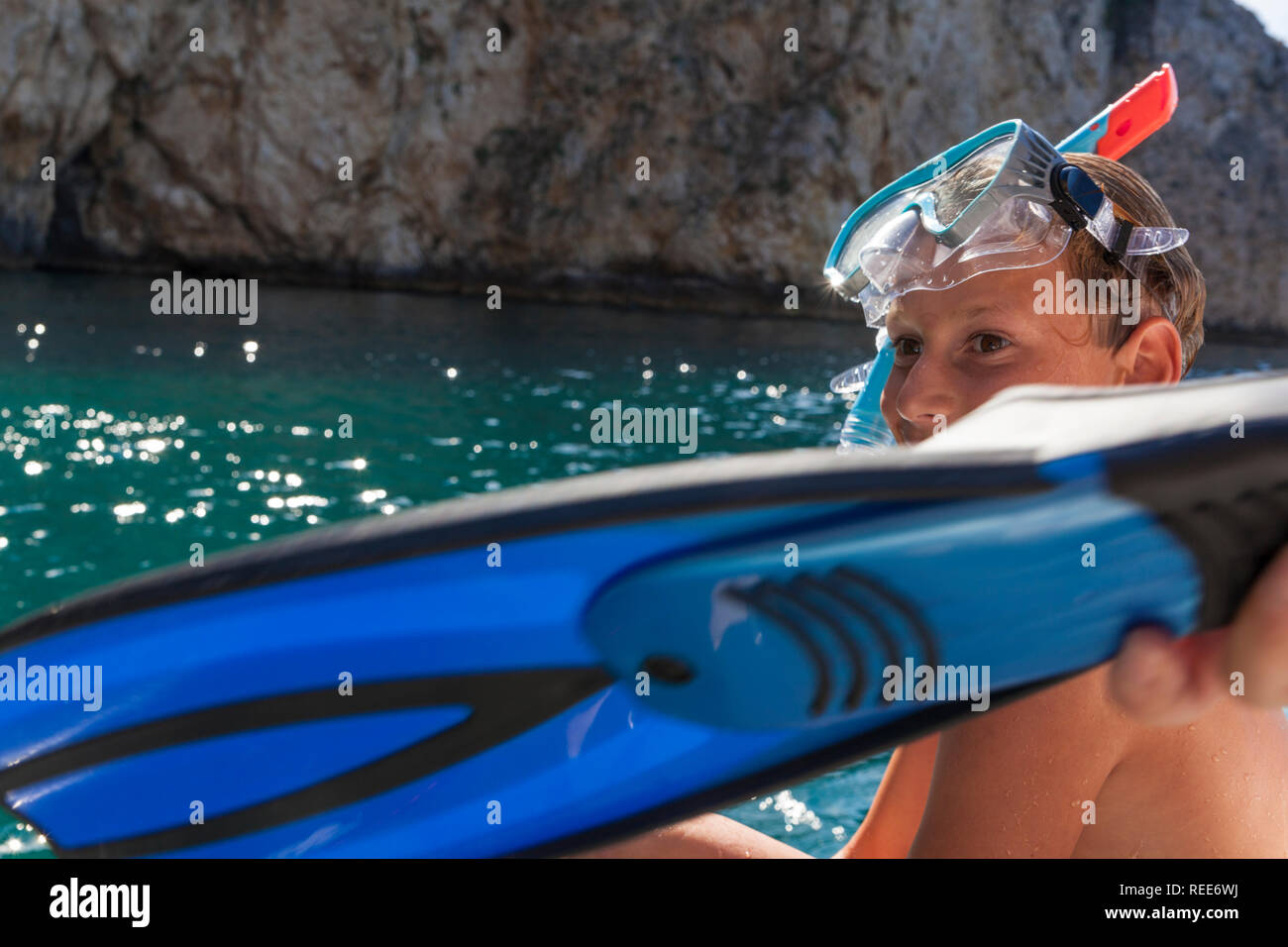 A cute boy with a swimming mask on his head putting on swimming fins - Stock Image