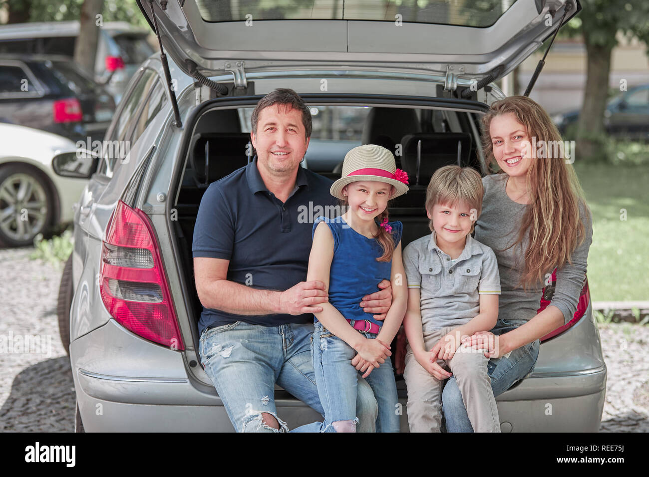 happy family sitting in the trunk of a family car - Stock Image