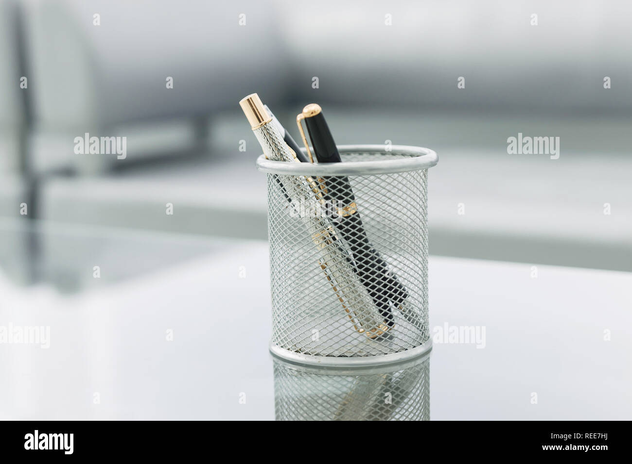 pencil stand and glasses on the glass Desk in the office Stock Photo