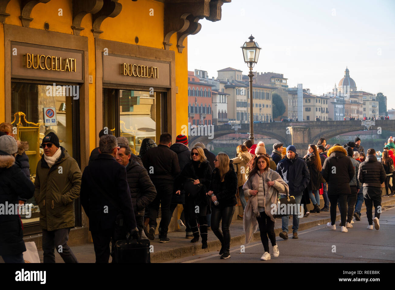 Italy Florence Firenze Lots of tourists walk along the Arno River near the Ponte Vecchio bridge and the Buccellati jewelry store in the winter - Stock Image