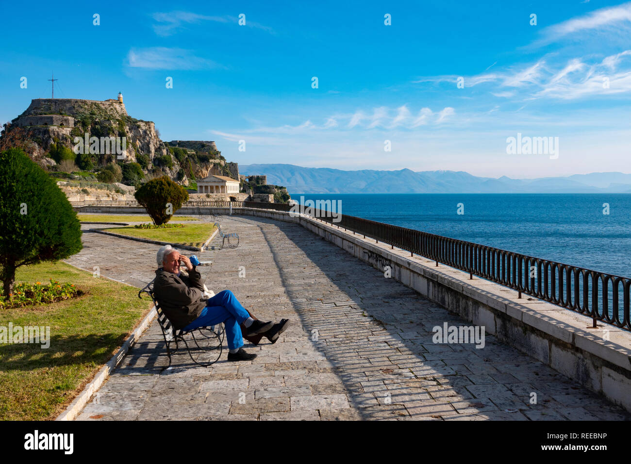 Greece Corfu Corfu Town an elderly couple sits along the seafront near the Old Fortress taking in the sun Stock Photo