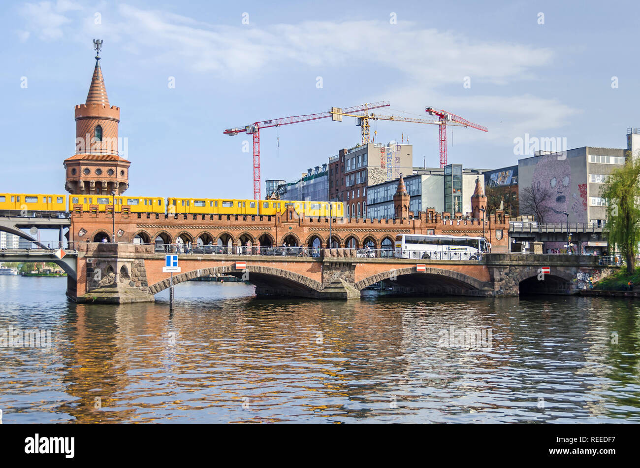 Berlin, Germany - April 22, 2018: Construction boom in the center of Berlin. View of the Brick Gothic Oberbaum Bridge with an U-Bahn train crossing it - Stock Image