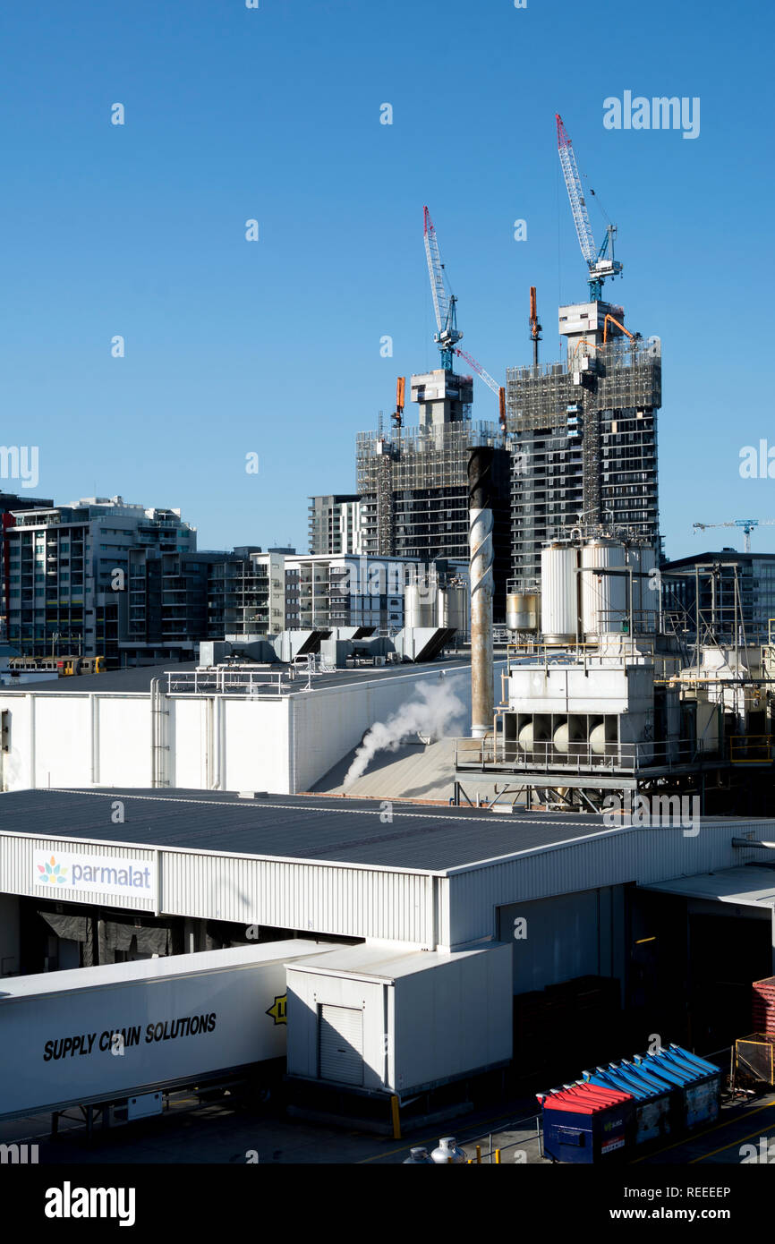 Parmalat milk factory with high-rise building construction in the distance, Brisbane, Queensland, Australia - Stock Image