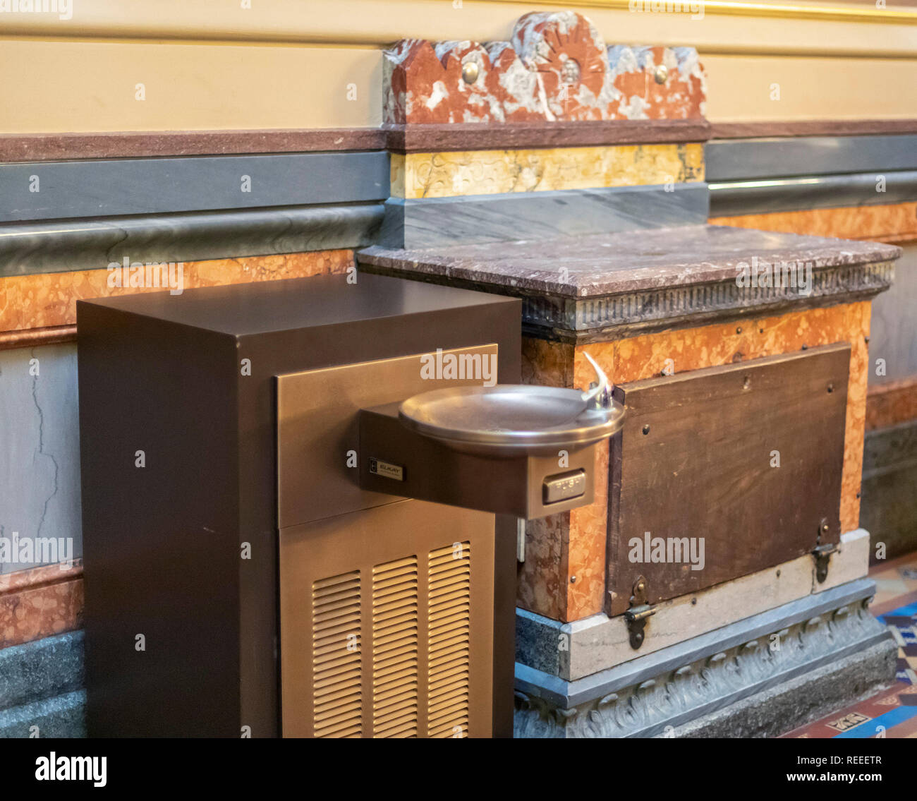 Des Moines, Iowa - A modern water fountain is next to one of the original water coolers in the Iowa state capitol building. The original cooler held a - Stock Image