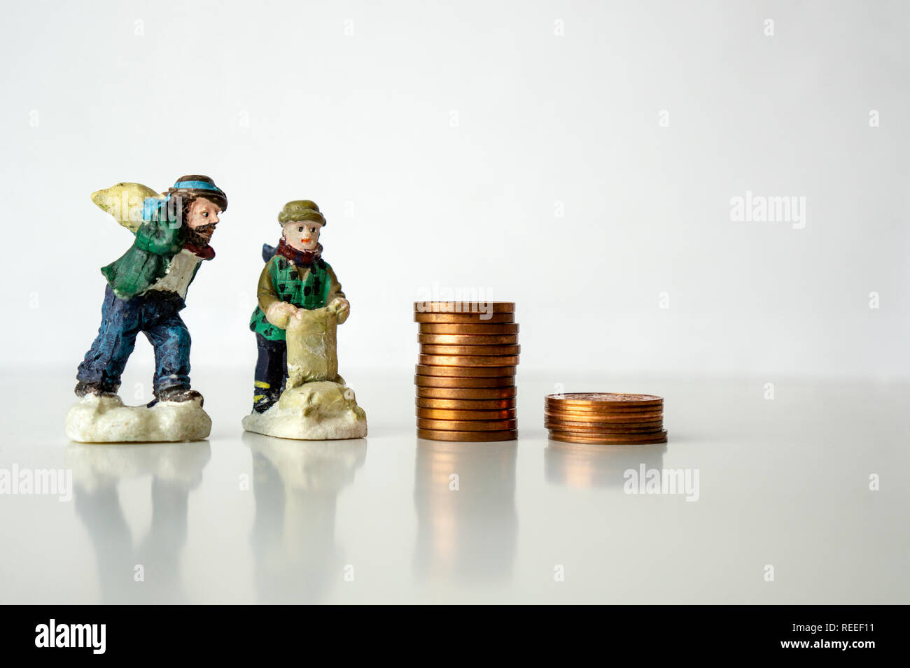 stack of coins with worker figures on white background Working for pennies cents concept Low salary Stock Photo