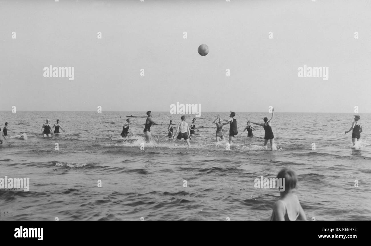 Summer in the 1920s. A group of people are playing ball in the water on a sunny day on the beach. Sweden 1920s Stock Photo