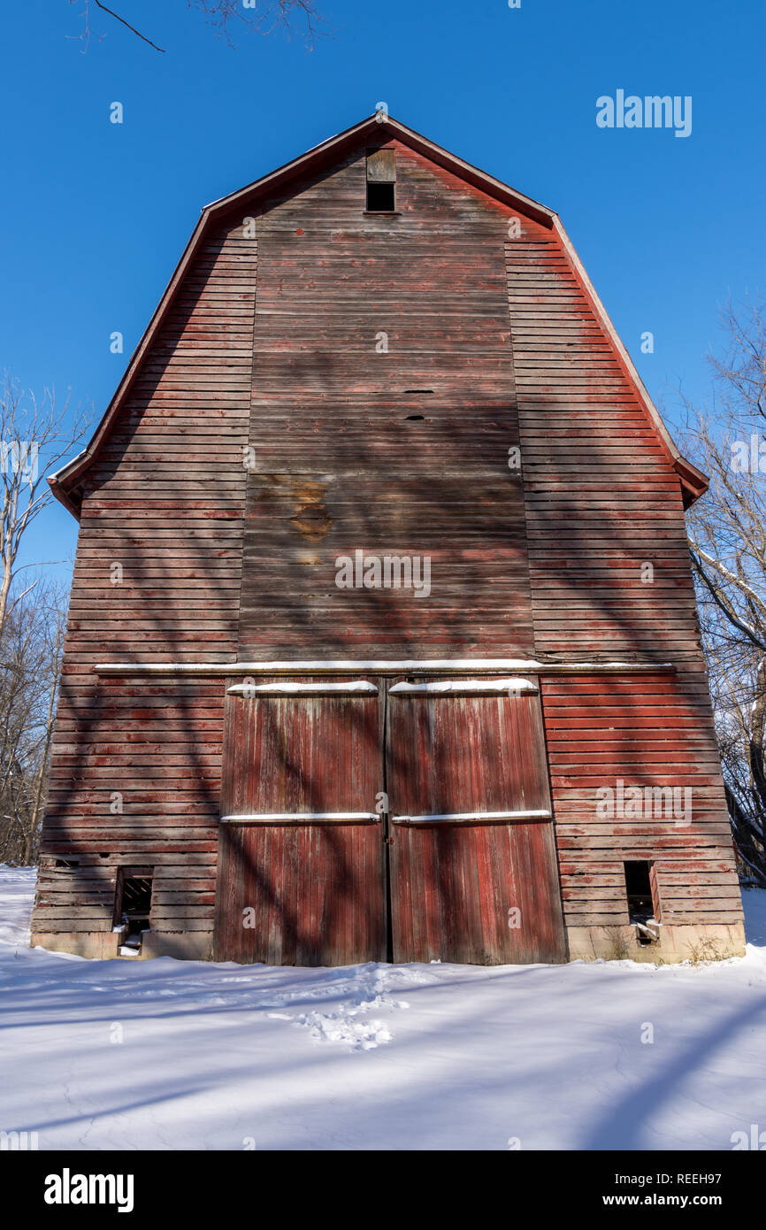 Large red barn hidden in the woods on a brutally cold winters day. - Stock Image