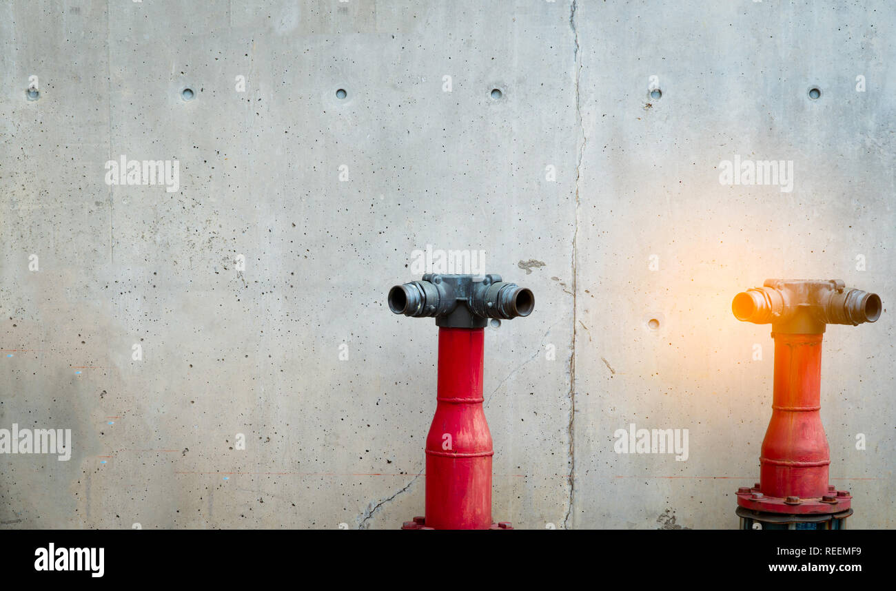 Fire safety pump on cement floor of concrete building. Deluge system of firefighting system. Plumbing fire protection. Red fire pump in front - Stock Image