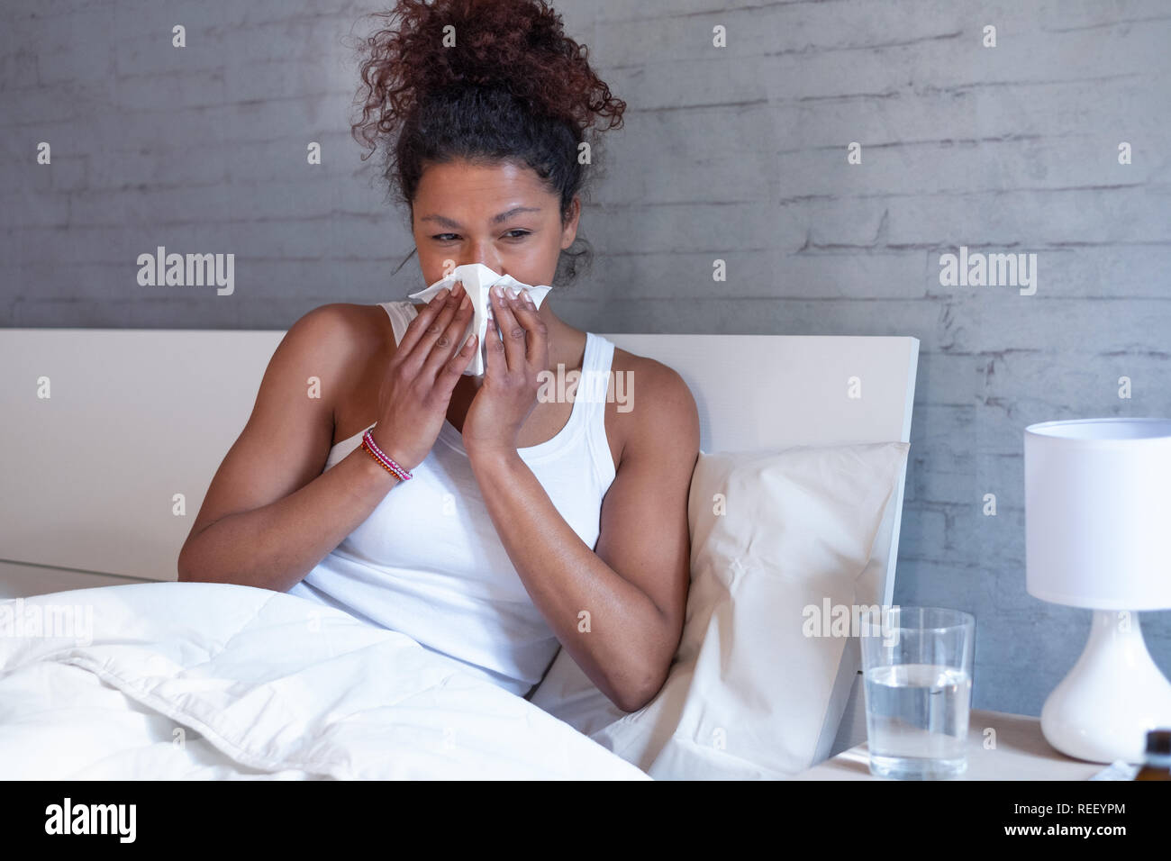 Sick african american girl with flu virus in bed at home - Stock Image