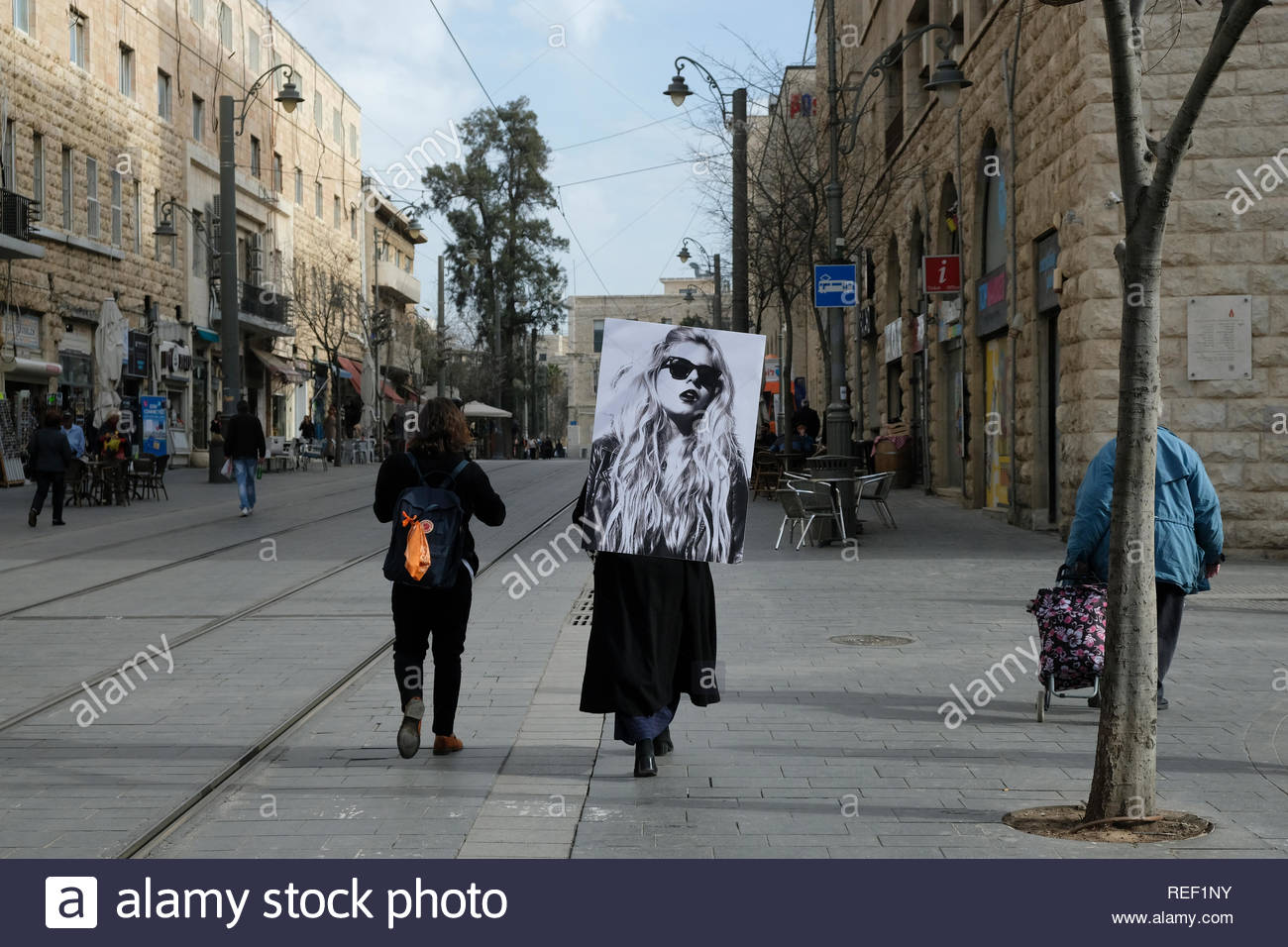 Young Israeli artist Korin Abisdris carrying a large portrait of herself on her back as a tribute to the work of Israeli artist Moti Mizrachi ( 1973) entitled 'Via Dolorosa' in Jaffa road the longest and oldest major streets in downtown West Jerusalem Israel - Stock Image