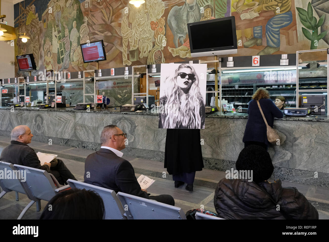 Young Israeli artist Korin Abisdris carrying a large portrait of herself on her back as a tribute to the work of Israeli artist Moti Mizrachi ( 1973) entitled 'Via Dolorosa' in the central post office in West Jerusalem Israel - Stock Image